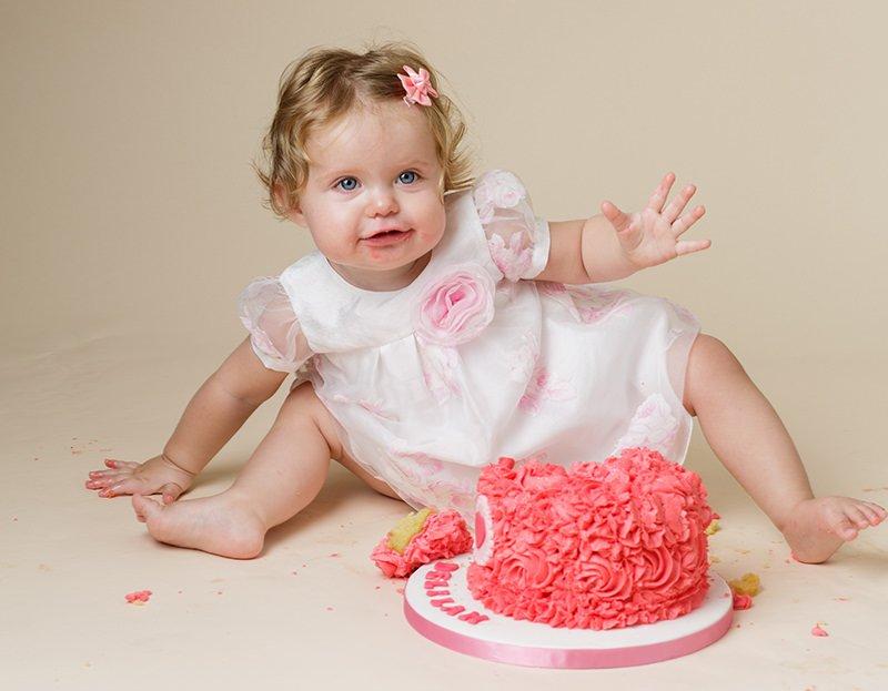1 year old enjoying making a cake smash mess with her birthday cake - cake smash photo session information