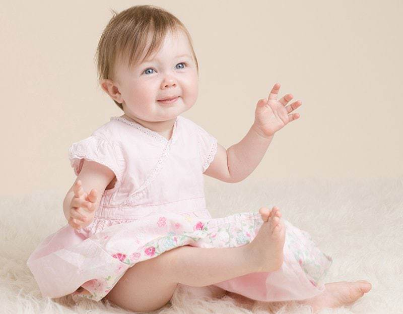 Sitting baby laughing & looking toward the camera - baby photo session information