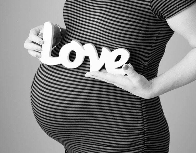 close up of a baby bump with mum to be's holding a 'love' sign - maternity photo session information
