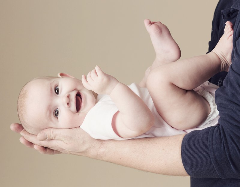 smiling baby in parents arms - watch me grow photo session information