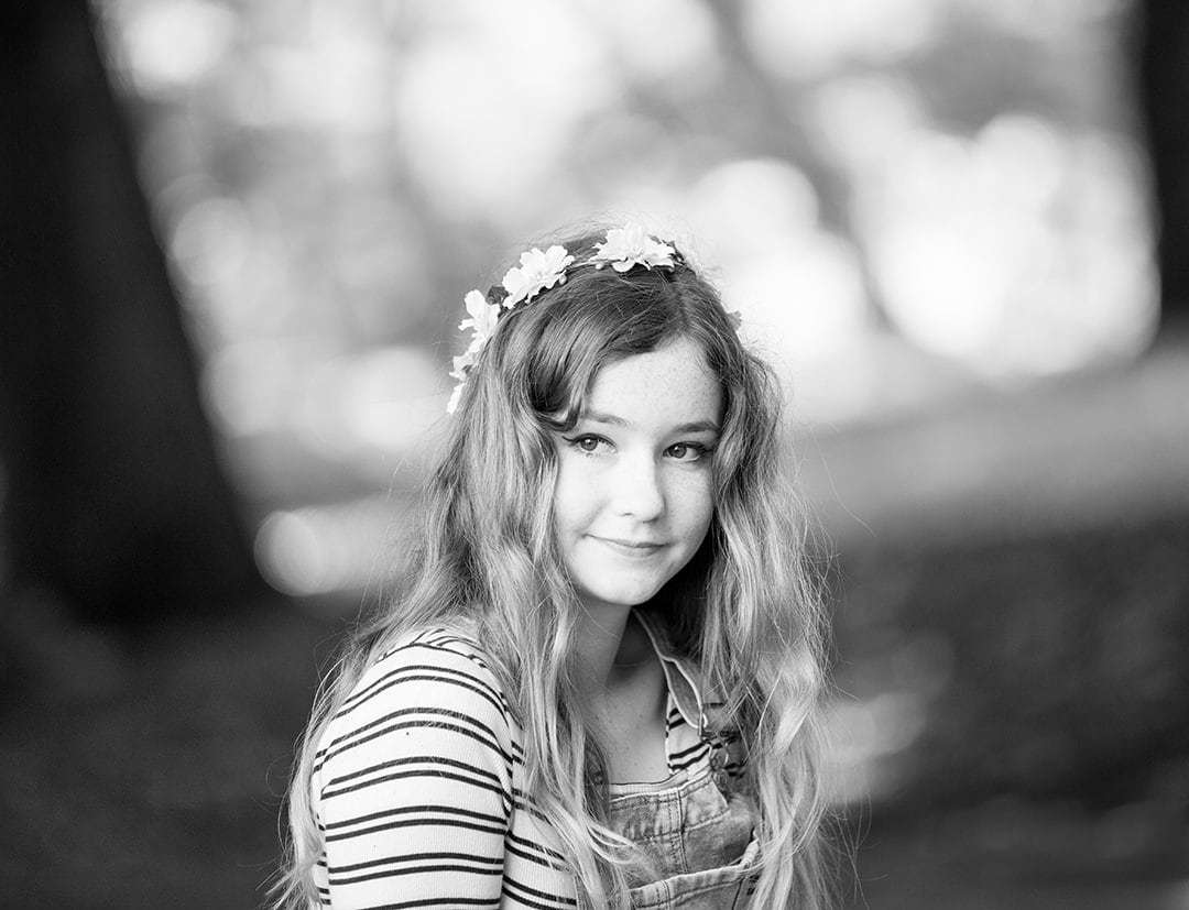 Black and white portrait of a young girl sat casually in a woodland park looking away from camera