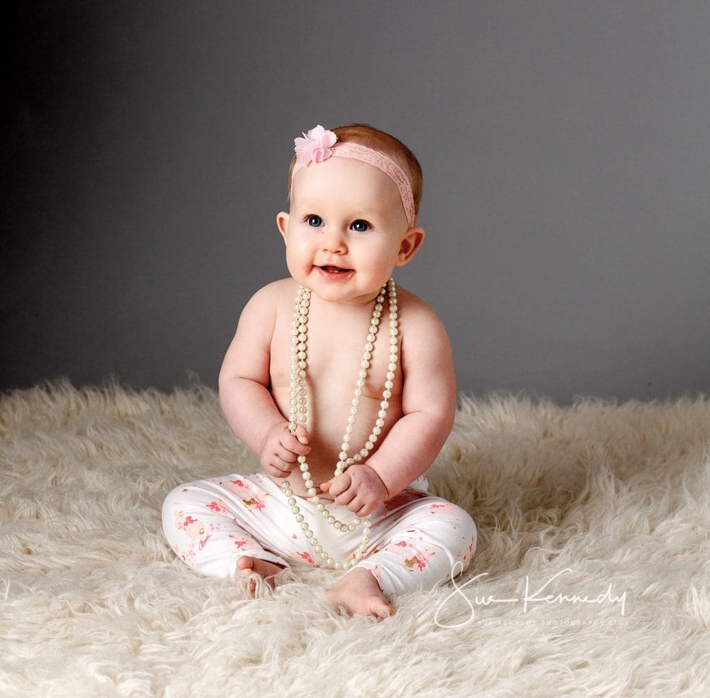 Baby girl sitting on rug playing with necklace - Baby club second session