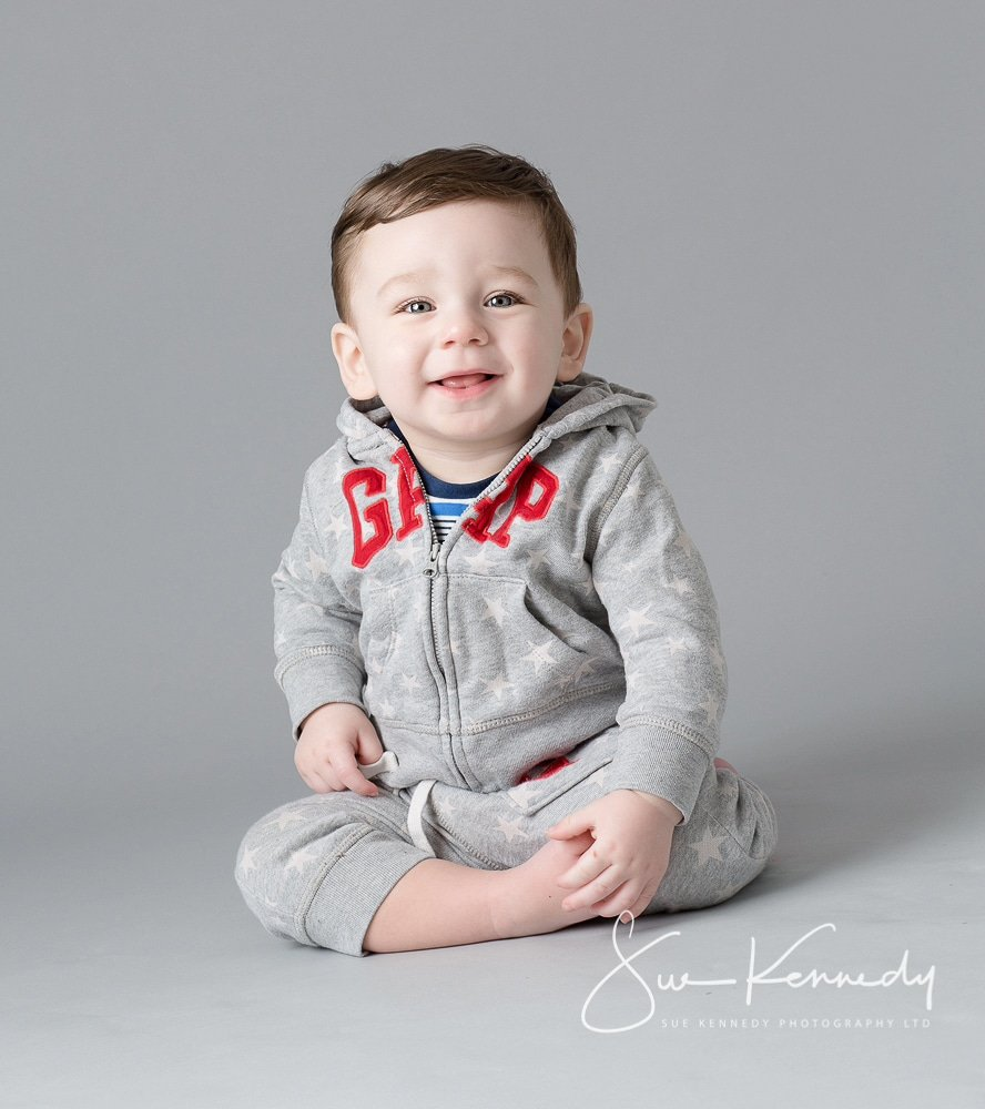 baby boy sitting crossed leg and smiling toward camera