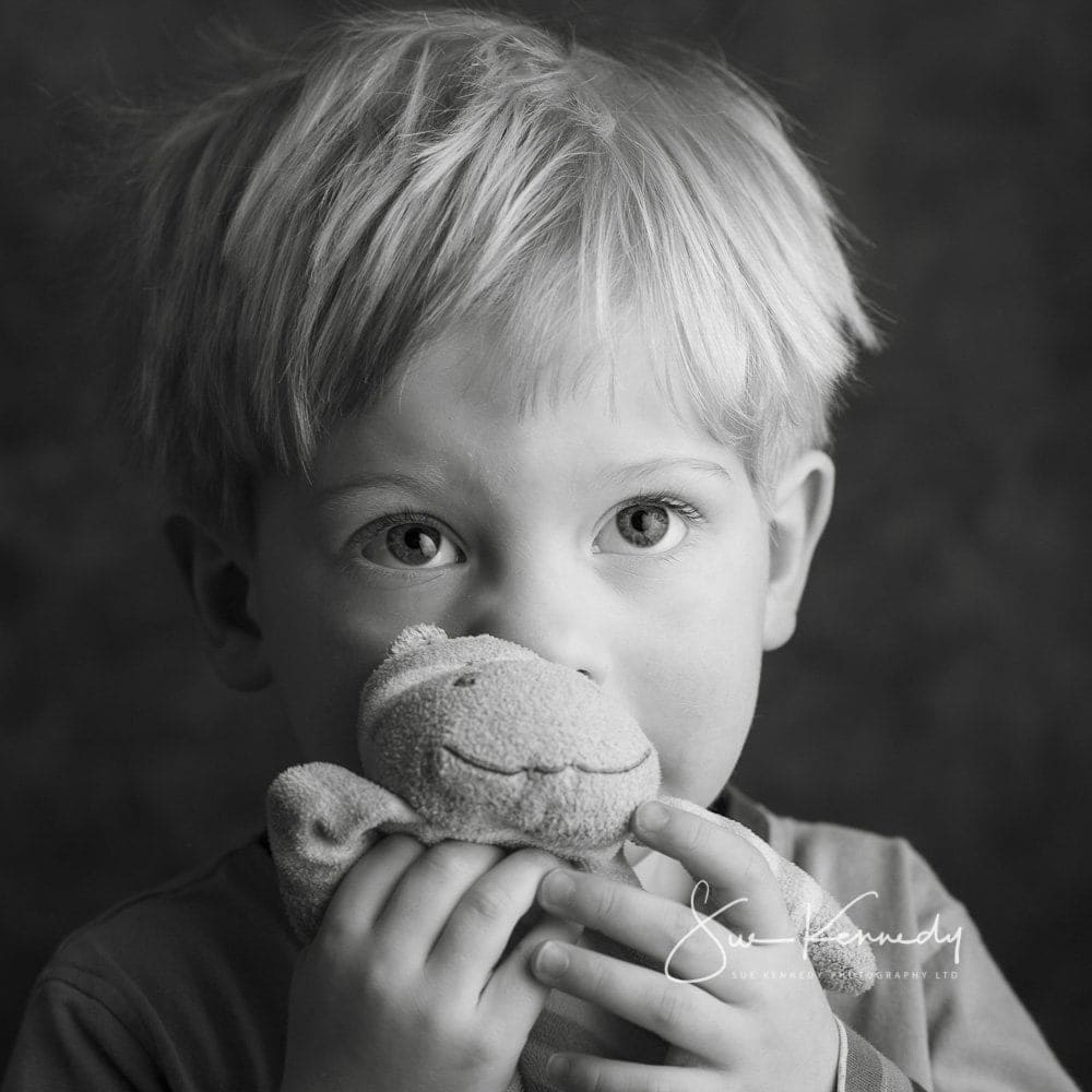 boy cuddling a soft toy in black and white