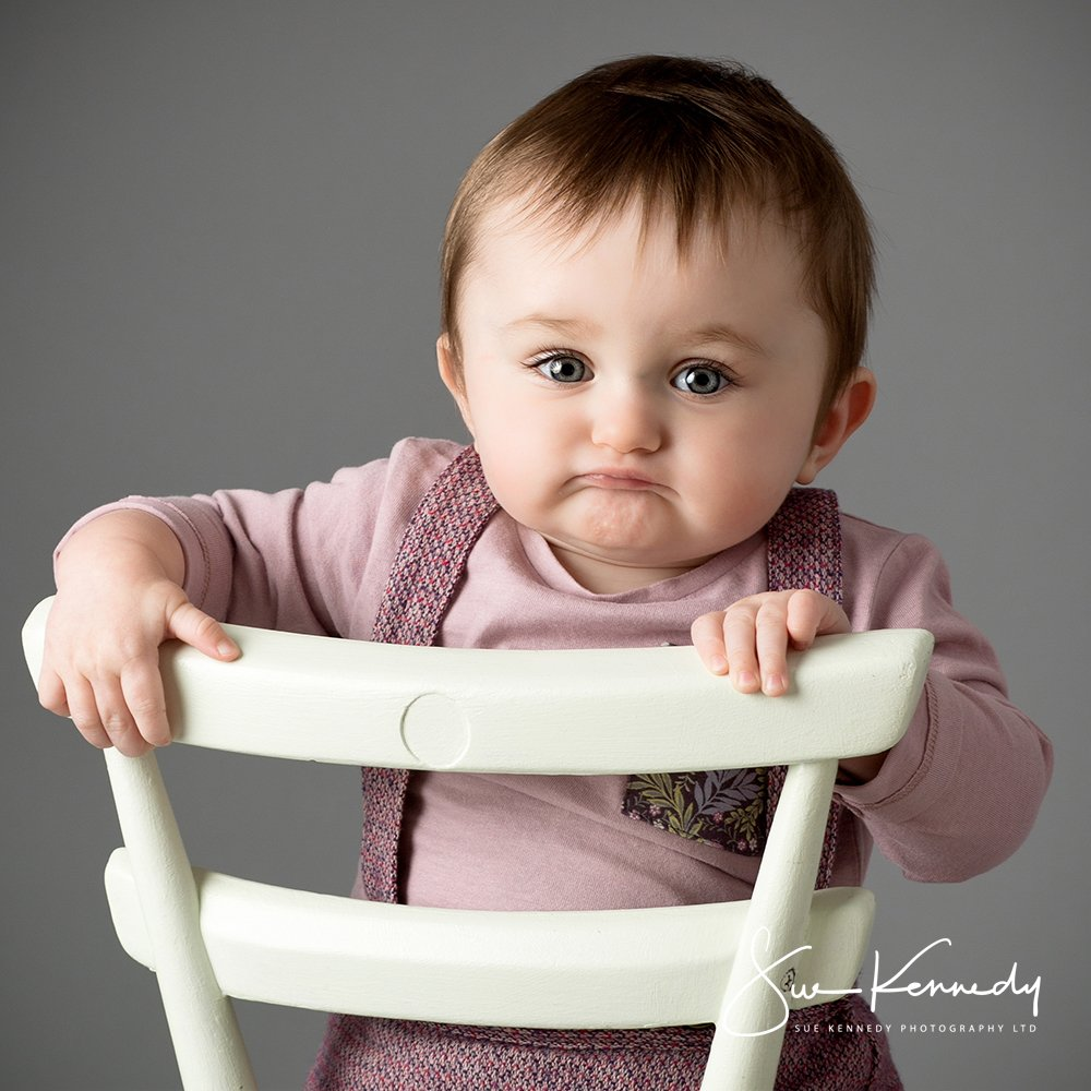 Baby girl sat on a child size chair making an expressive face