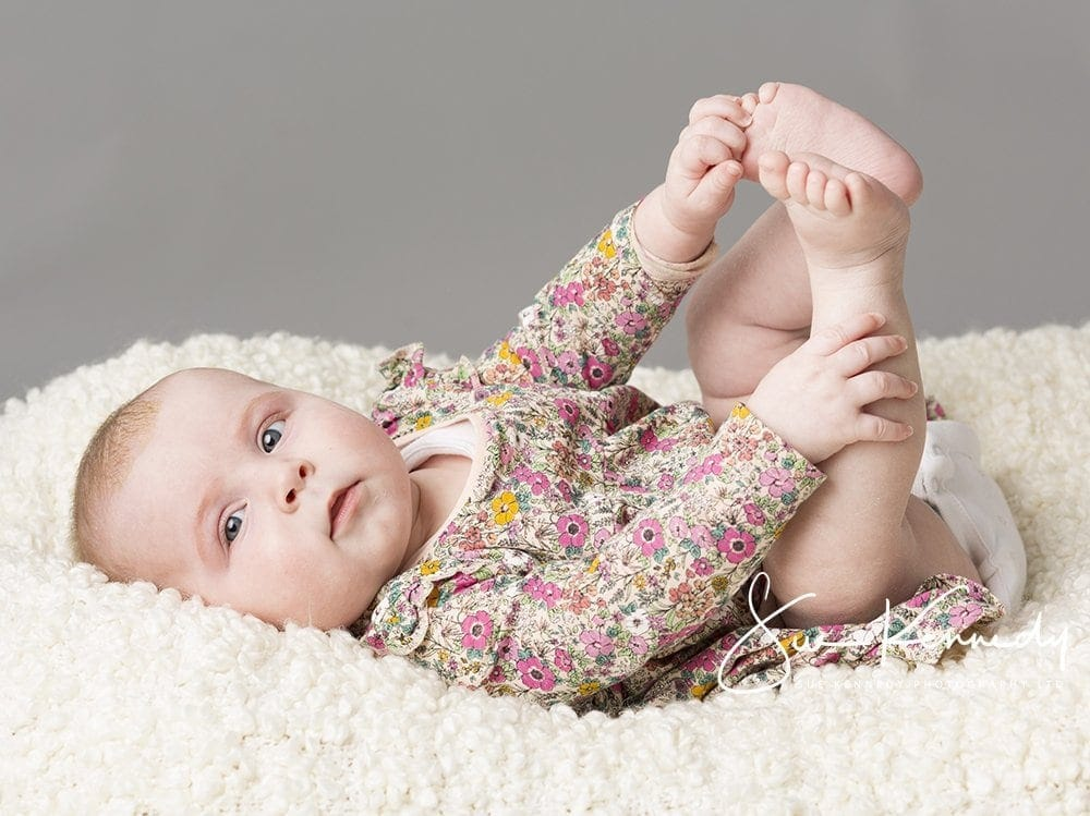 Newborn Baby Photography of Baby girl lying and grabbing her toes
