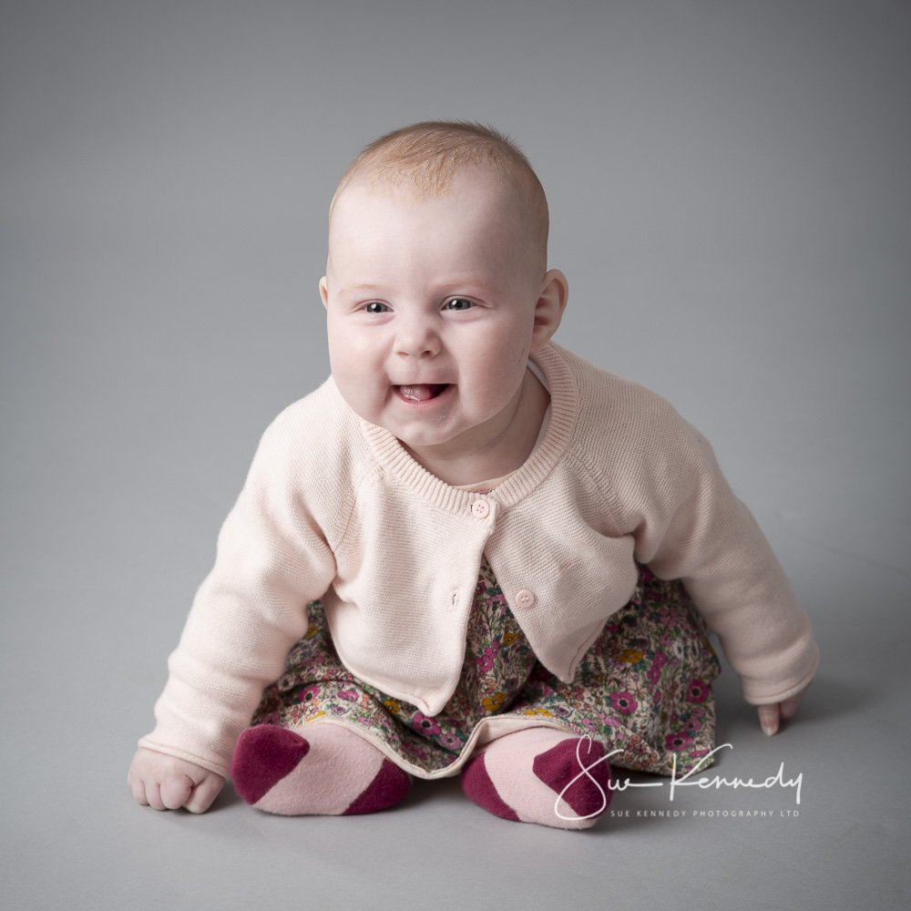 sitting baby smiling and leaning forward