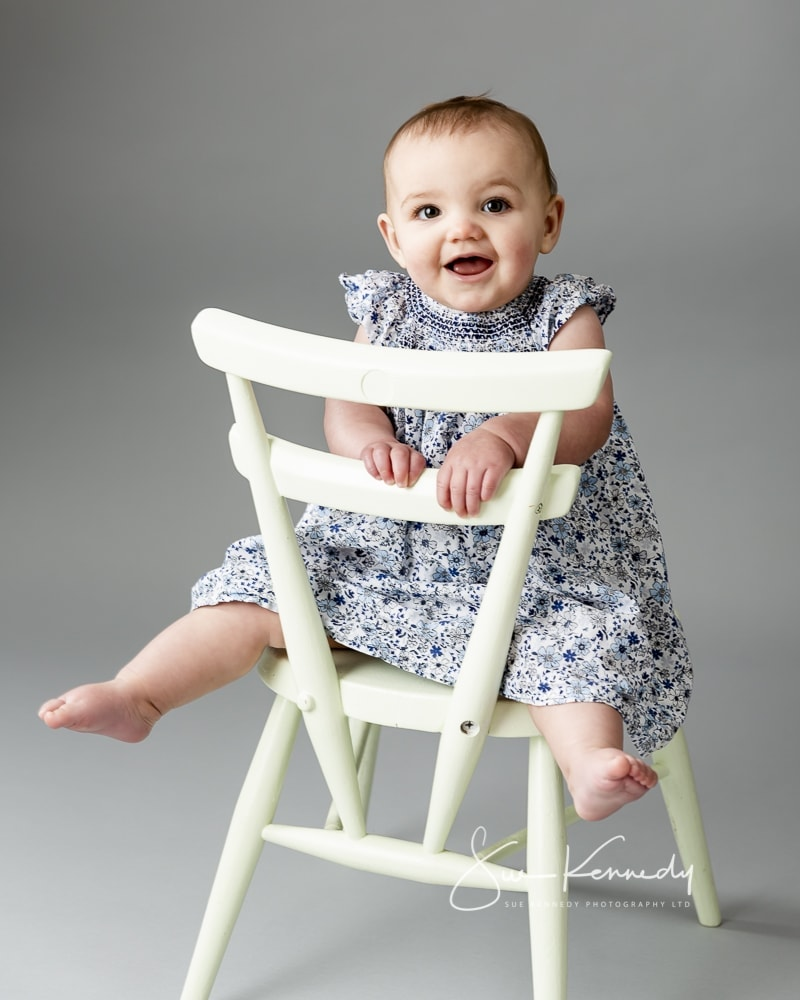 classic pose of a baby on a chair smiling