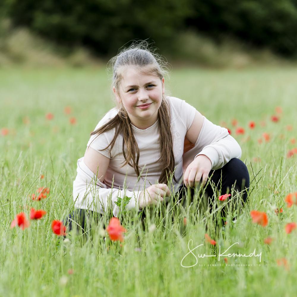 outdoor image of girl in a poppy field