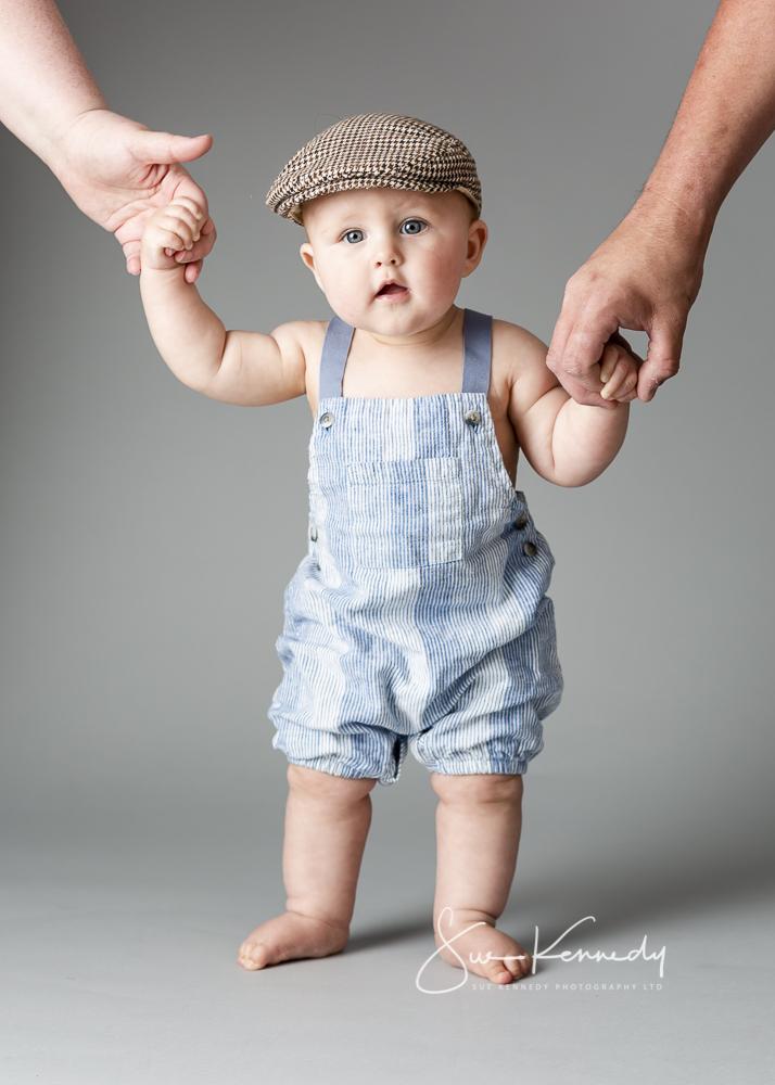 Portfolio photo of toddler boy standing holding parents hands